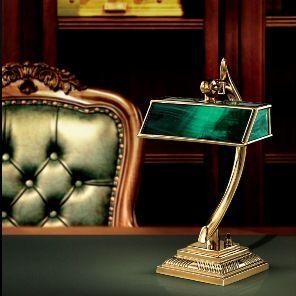 Vergoldete Tischlampe in grüner Bankerslampoptik auf einem edlen Schreibtisch mit Sessel