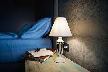 Helle Tischlampe mit Buch und Brille neben einem blauen Bett