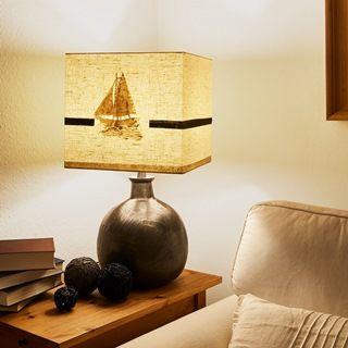 Eingeschaltete Tischlampe mit Sandmotiv eines Bootes neben Dekoelementen