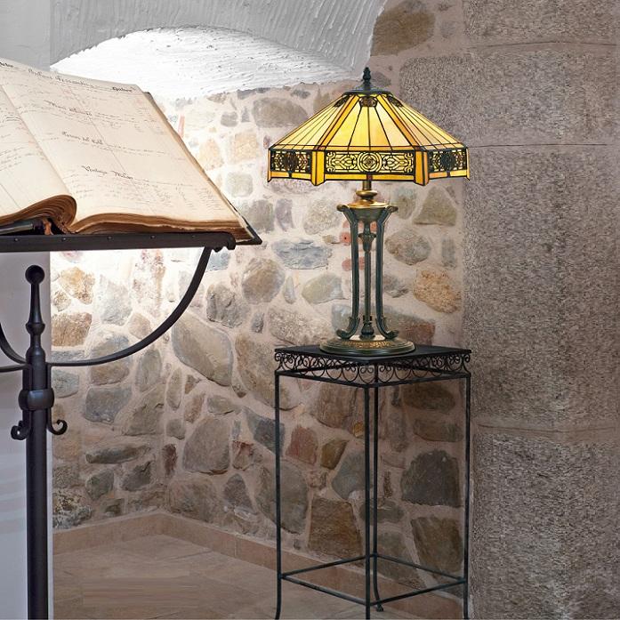 Goldene Tiffany-Tischlampe auf Tisch neben einem Notenständer in einem steinernen Keller