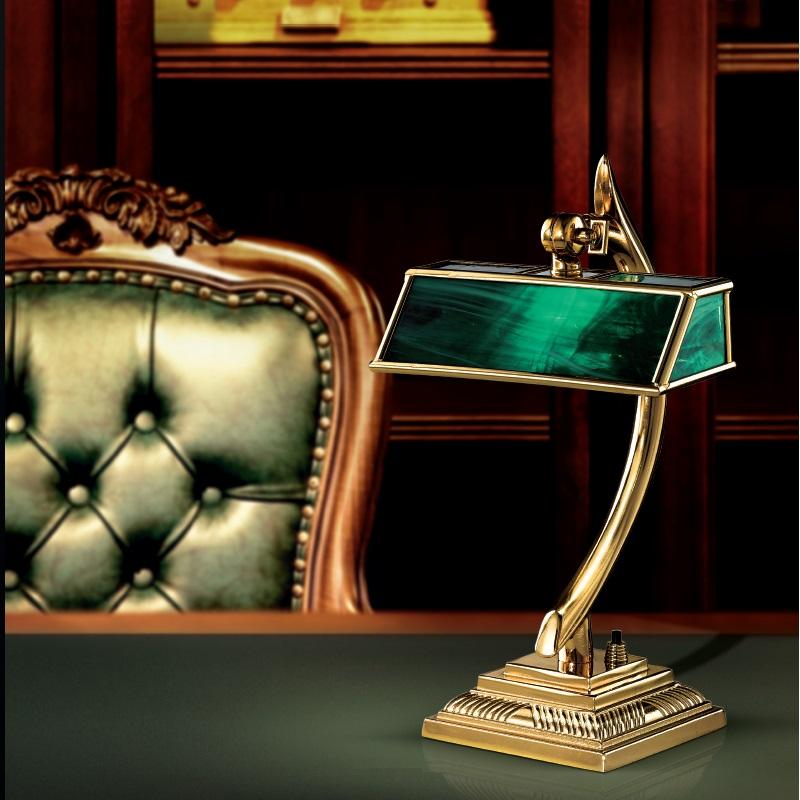 Tischlampe in grüner Bankerslampoptik auf einem edlen Schreibtisch mit Sessel